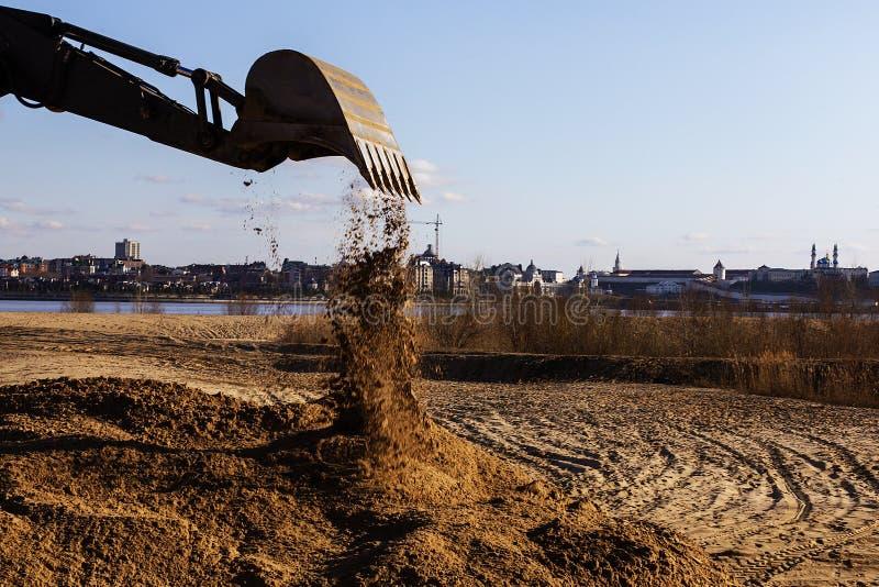 Το τρακτέρ χύνει το αμμοχάλικο από τον κάδο στοκ φωτογραφία