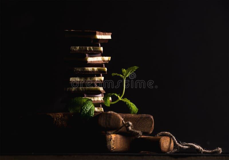 Το τριπλάσιο ο σωρός ή ο πύργος κομματιών σοκολάτας με το banch της φρέσκιας μέντας στο μαύρο υπόβαθρο στοκ εικόνες με δικαίωμα ελεύθερης χρήσης