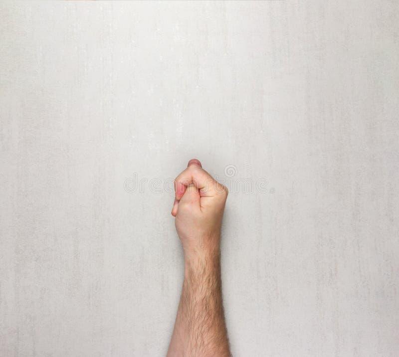 Το τριχωτό χέρι ατόμων παρουσιάζει τη χειρονομία ενός σύκου σε ένα γκρίζο υπόβαθρο στοκ φωτογραφία