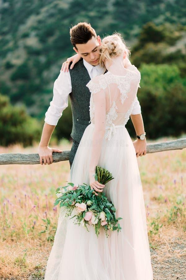 Το τρομερό πορτρέτο της νύφης και ο νεόνυμφος αγκαλιάζουν το ένα το άλλο τρυφερό στοκ εικόνα
