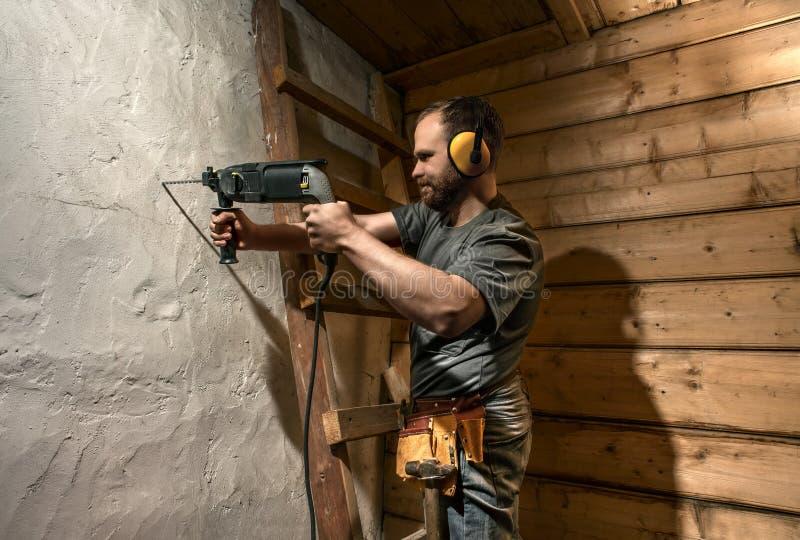 Το τρυπάνι εργατών οικοδομών διατρυπά το συμπαγή τοίχο στοκ φωτογραφίες