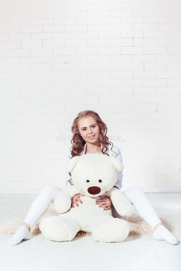 Το τρυφερό ξανθό αγκάλιασμα κοριτσιών teddy αντέχει στοκ φωτογραφία με δικαίωμα ελεύθερης χρήσης