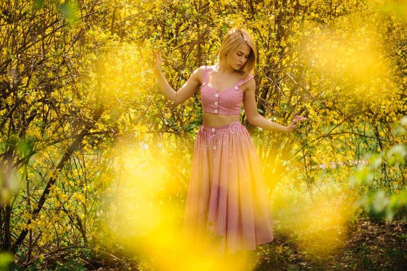 Το τρυφερό πορτρέτο μιας νέας ξανθής γυναίκας έντυσε σε ένα ρόδινο φόρεμα που στέκεται κοντά στο κίτρινο ανθίζοντας δέντρο στοκ φωτογραφία με δικαίωμα ελεύθερης χρήσης