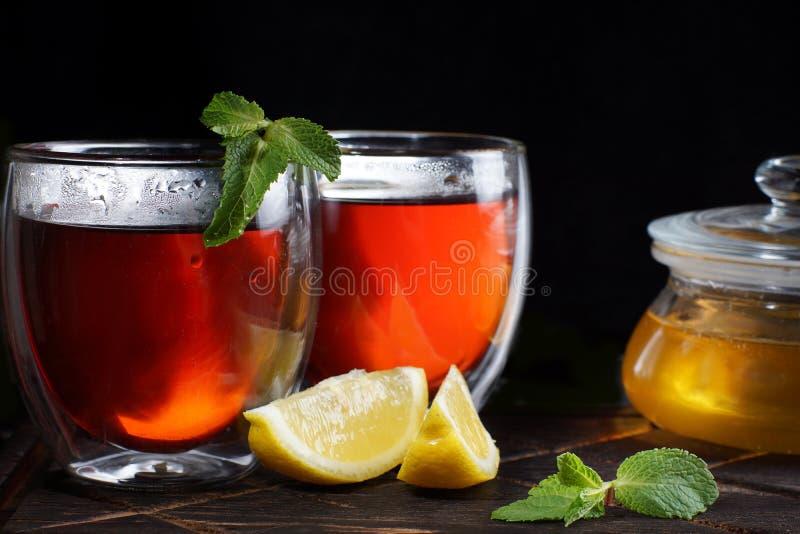 Το τσάι, που χύνεται στα θερμικά γυαλιά, κοντά σε ένα βάζο του μελιού, ένα κλαδάκι της μέντας και μια φέτα του λεμονιού στοκ εικόνες με δικαίωμα ελεύθερης χρήσης