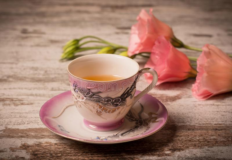 Το τσάι σε ένα φλυτζάνι ραχών και ένα ροζ ανθίζει στο ξύλινο υπόβαθρο στοκ εικόνες