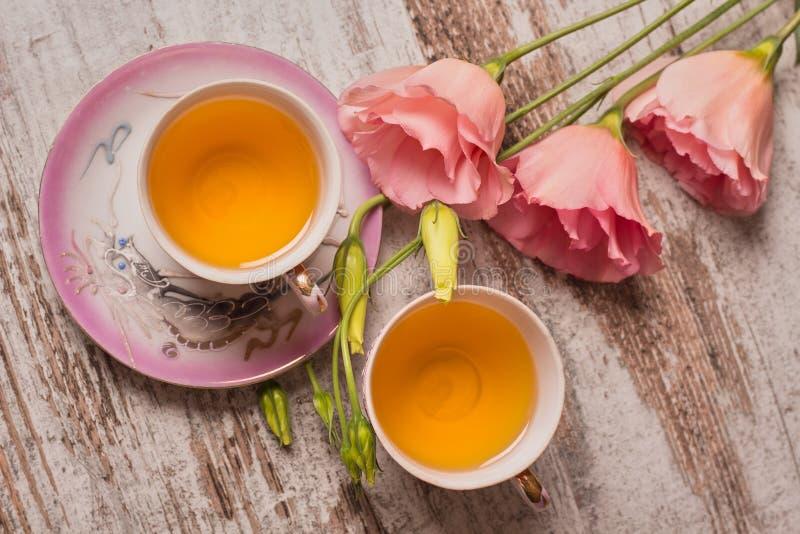 Το τσάι στα φλυτζάνια ραχών και ένα ροζ ανθίζει στο ξύλινο υπόβαθρο στοκ φωτογραφίες με δικαίωμα ελεύθερης χρήσης