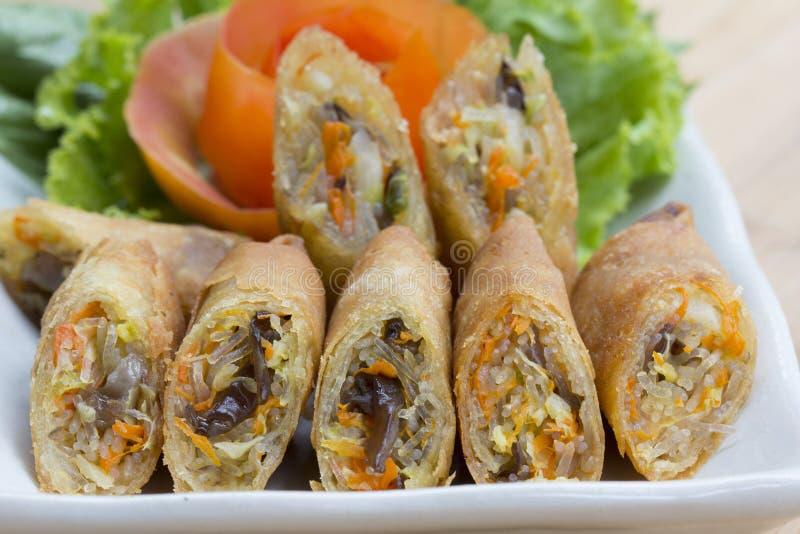 Το τσιγαρισμένο ελατήριο κυλά, Por Pieer Tod ή τηγανισμένος ρόλος ανοίξεων ρόλων άνοιξη ταϊλανδικός στο άσπρο πιάτο στον ξύλινους στοκ εικόνα με δικαίωμα ελεύθερης χρήσης
