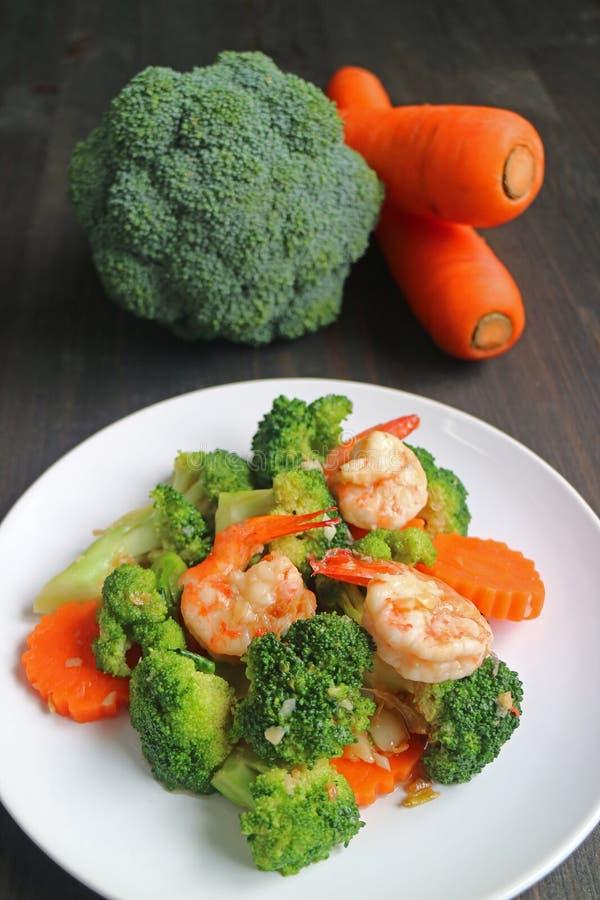 Το υγιές πιάτο της γαρίδας ανακατώνει τηγανισμένος με το μπρόκολο και το καρότο που εξυπηρετούνται στο άσπρο πιάτο στοκ εικόνες