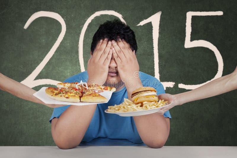 Το υπέρβαρο άτομο αποφεύγει τις τροφές χωρίς θρεπτική αξία το 2015 στοκ εικόνες