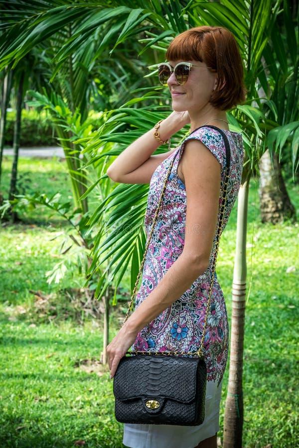 Το υπαίθριο πορτρέτο μόδας της αισθησιακής νέας μοντέρνης κυρίας γοητείας στα γυαλιά ηλίου με το χειροποίητο snakeskin πολυτέλεια στοκ εικόνα