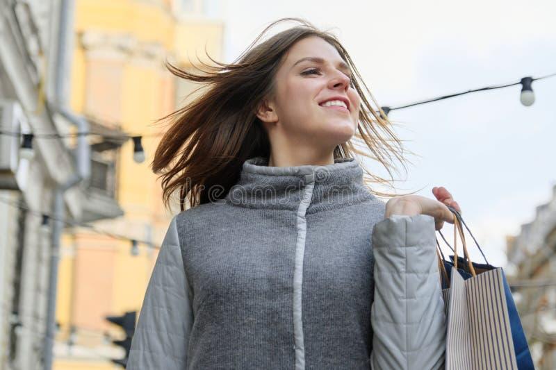 Το υπαίθριο πορτρέτο της νέας όμορφης χαμογελώντας γυναίκας με τις αγορές τοποθετεί την κινηματογράφηση σε πρώτο πλάνο, αγορές άν στοκ εικόνα