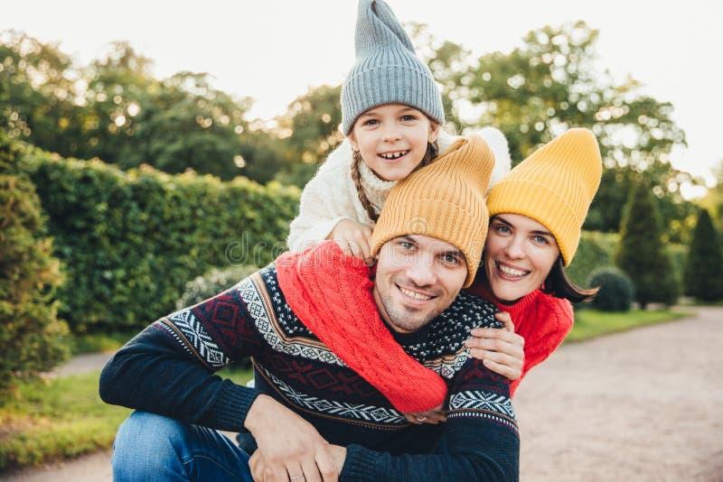 Το υπαίθριο πορτρέτο του όμορφου ατόμου δίνει το σηκώνω στην πλάτη στη σύζυγό του και η κόρη, φορά τα θερμά ενδύματα, έχει τις ευ στοκ φωτογραφία