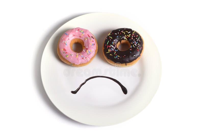 Το λυπημένο πρόσωπο Smiley έκανε στο πιάτο με τα donuts ως μάτια και το στόμα σιροπιού σοκολάτας στη γλυκές διατροφή και τη διατρ στοκ εικόνες