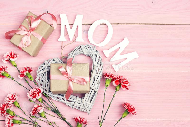 Το υπόβαθρο ημέρας μητέρων ` s με το γαρίφαλο ανθίζει και δώρων κιβώτια στο ρόδινο ξύλινο πίνακα στοκ φωτογραφία