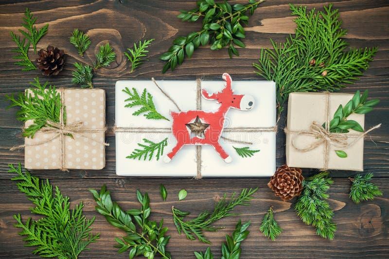 Το υπόβαθρο Χριστουγέννων με επεξεργασμένα τα χέρι δώρα, παρουσιάζει στον αγροτικό ξύλινο πίνακα Υπερυψωμένος, επίπεδος βάλτε, το στοκ φωτογραφία