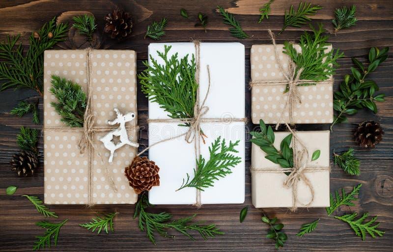 Το υπόβαθρο Χριστουγέννων με επεξεργασμένα τα χέρι δώρα, παρουσιάζει στον αγροτικό ξύλινο πίνακα Υπερυψωμένος, επίπεδος βάλτε, το στοκ φωτογραφία με δικαίωμα ελεύθερης χρήσης