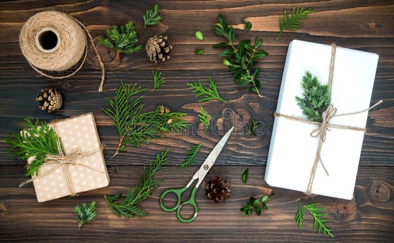 Το υπόβαθρο Χριστουγέννων με επεξεργασμένα τα χέρι δώρα, παρουσιάζει στον αγροτικό ξύλινο πίνακα Υπερυψωμένος, επίπεδος βάλτε, το στοκ εικόνα