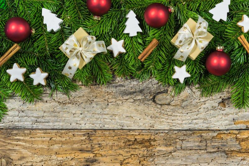 Το υπόβαθρο Χριστουγέννων με τα κιβώτια δώρων, έλατο διακλαδίζεται σύνορα, μπισκότα αστεριών και διακοσμήσεις στοκ εικόνα με δικαίωμα ελεύθερης χρήσης