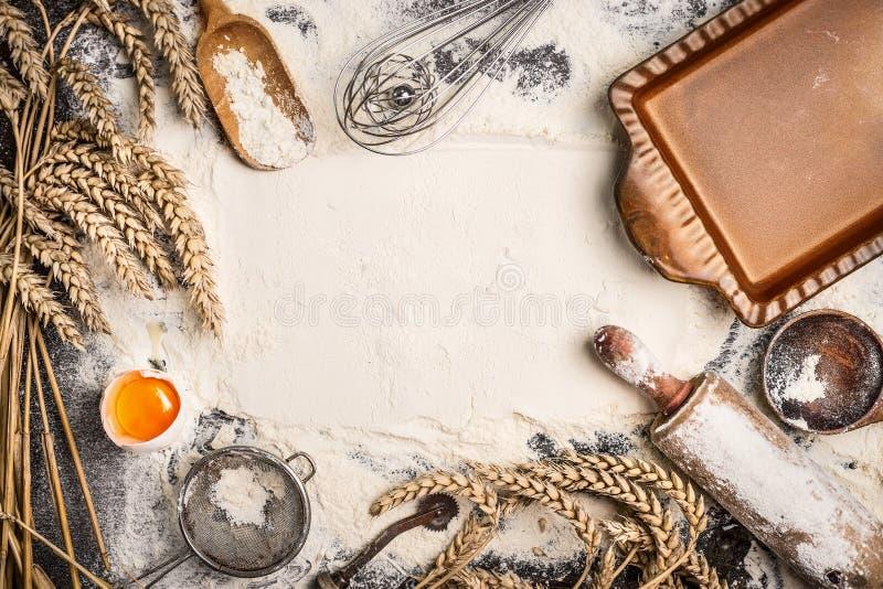 Το υπόβαθρο ψησίματος αλευριού με το ακατέργαστο αυγό, κυλώντας καρφίτσα, αυτί σίτου και αγροτικός ψήνει το τηγάνι στοκ εικόνες
