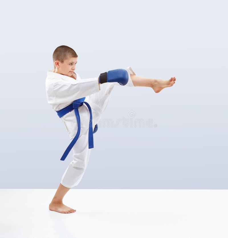 Το υψηλό μπροστινό karateka λακτίσματος κτυπά στο karategi στοκ φωτογραφία