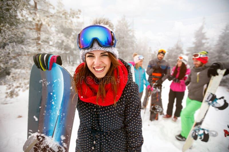 Το φίλαθλο θηλυκό κρατά το σνόουμπορντ στα βουνά στο χειμώνα στοκ φωτογραφία με δικαίωμα ελεύθερης χρήσης