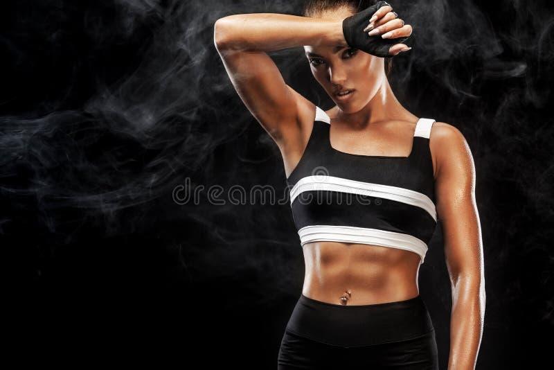 Το φίλαθλο όμορφο αφροαμερικανός πρότυπο, γυναίκα σε sportwear κάνει την ικανότητα ασκώντας στο μαύρο υπόβαθρο για να μείνει κατά στοκ φωτογραφία με δικαίωμα ελεύθερης χρήσης