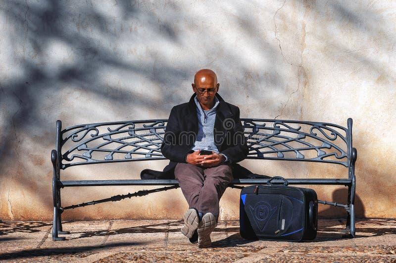 Το φαλακρό άτομο με το κιβώτιο smartphone και ταξιδιού κάθεται σε έναν παλαιό πάγκο σιδήρου στοκ εικόνες