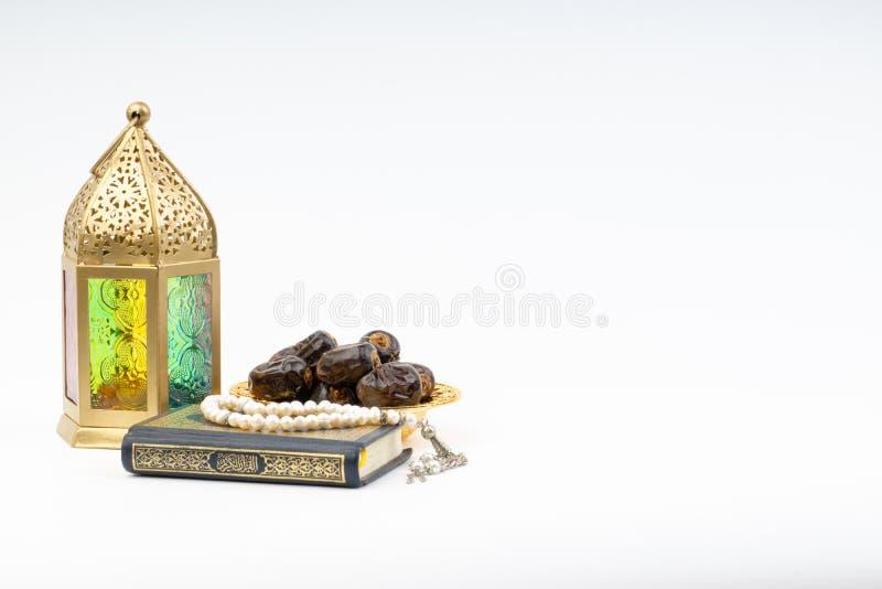 Το φανάρι, οι ημερομηνίες, Koran και Rosary στο άσπρο υπόβαθρο με την εκλεκτική εστίαση και τη συγκομιδή τεμαχίζουν στοκ εικόνα