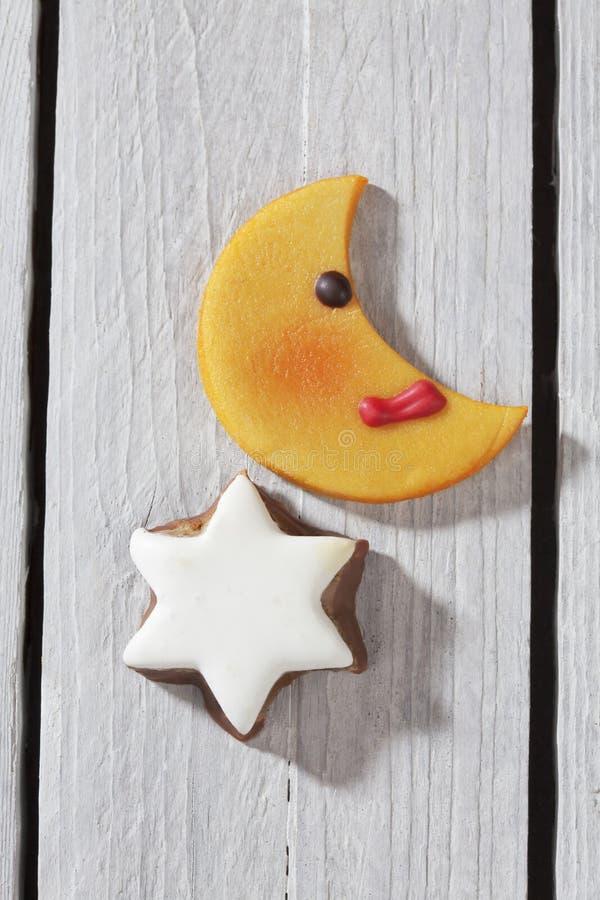 Το φεγγάρι διαμόρφωσε τη στενή επάνω ανυψωμένη άποψη αστεριών μπισκότων και κανέλας σχετικά με το ξύλινο υπόβαθρο στοκ εικόνες