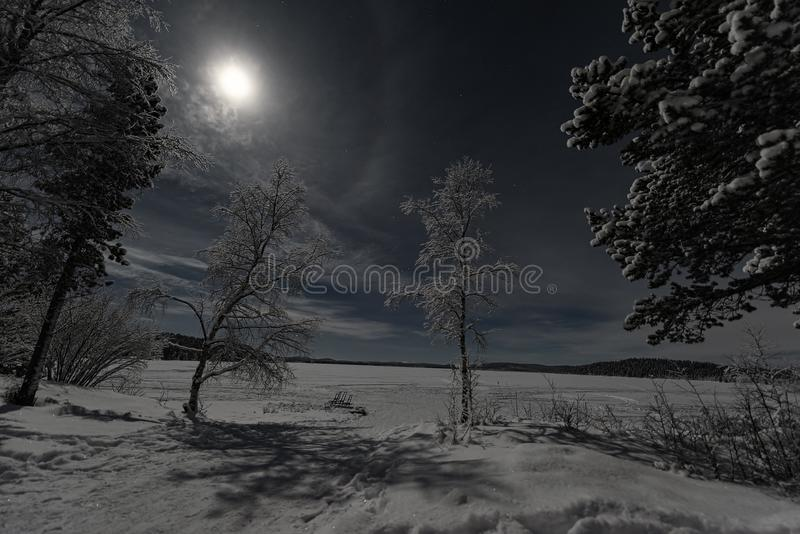Το φεγγαρόφωτο χειμερινό τοπίο Lappish με το δάσος και η λίμνη στο μπλε ουρανό με το πλήρες σύννεφο κάλυψαν το έξοχο φεγγάρι στοκ φωτογραφίες