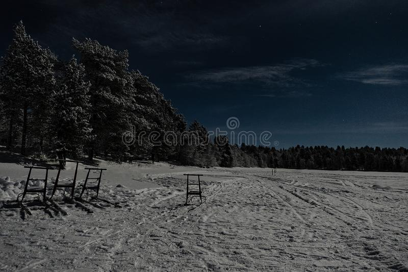 Το φεγγαρόφωτο χειμερινό τοπίο Lappish με το δάσος και η λίμνη στο μπλε ουρανό με το πλήρες σύννεφο κάλυψαν το έξοχο φεγγάρι στοκ εικόνα με δικαίωμα ελεύθερης χρήσης