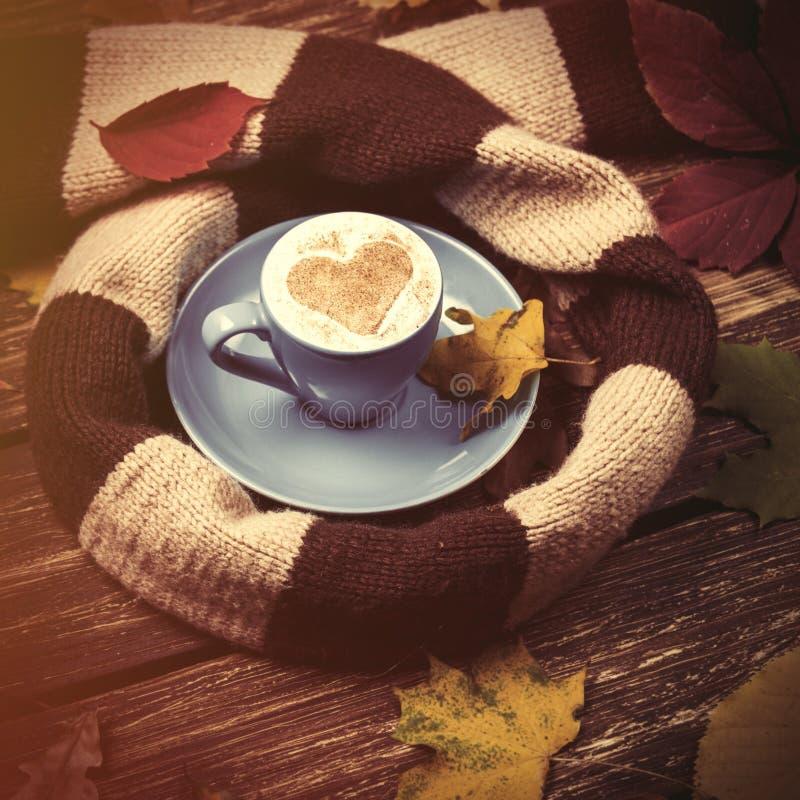 Το φθινόπωρο βγάζουν φύλλα, το φλυτζάνι μαντίλι και καφέ στον πίνακα στοκ φωτογραφία με δικαίωμα ελεύθερης χρήσης
