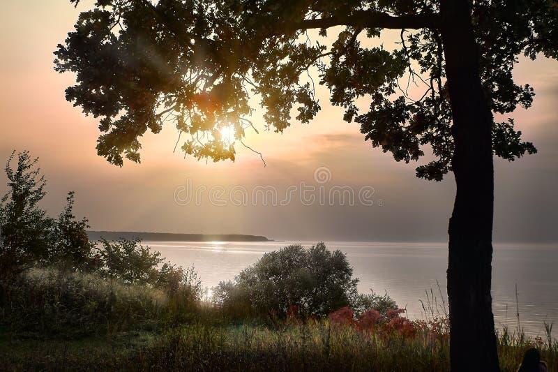 Το φθινόπωρο είναι χαρά, ή θλίψη; Ακτίνες του ήλιου ρύθμισης πέρα από τον ποταμό Ρωσία του Βόλγα στοκ εικόνα