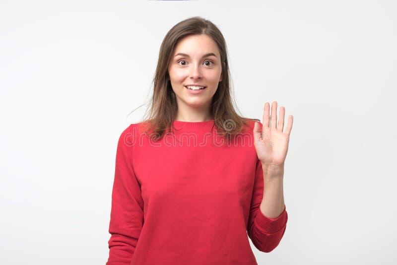 Το φιλικός-κοίταγμα έφηβος έντυσε στο κόκκινο pulover λέγοντας γειά σου, κυματίζοντας το χέρι της στοκ φωτογραφίες
