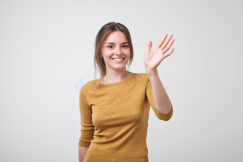 Το φιλικός-κοίταγμα ευρωπαϊκός έφηβος έντυσε στο κίτρινο pulover λέγοντας γειά σου, κυματίζοντας το χέρι της στοκ φωτογραφία με δικαίωμα ελεύθερης χρήσης