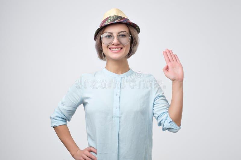 Το φιλικός-κοίταγμα ευρωπαϊκός έφηβος έντυσε στο μπλε πουκάμισο λέγοντας γειά σου, κυματίζοντας το χέρι της στοκ φωτογραφία με δικαίωμα ελεύθερης χρήσης
