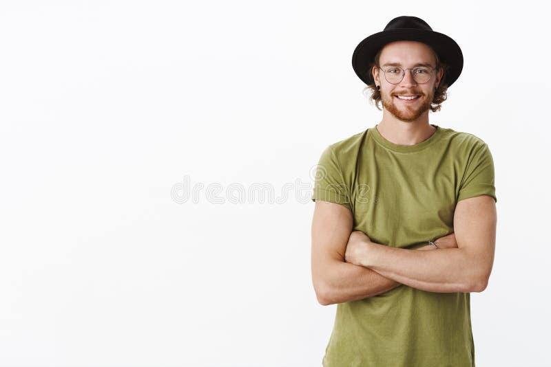 Το φιλικός-κοίταγμα ευχαρίστησε και ηρεμεί το όμορφο γενειοφόρο αρσενικό στα γυαλιά και το καπέλο χαμογελώντας χαρωπά να απολαύσε στοκ εικόνα με δικαίωμα ελεύθερης χρήσης