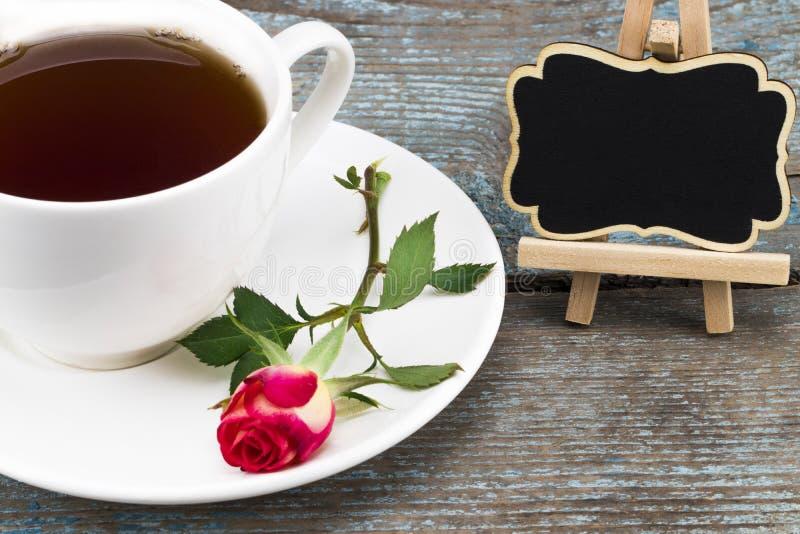 Το φλυτζάνι καφέ και κόκκινος αυξήθηκε με τον πίνακα με το κενό διάστημα για το α στοκ εικόνες