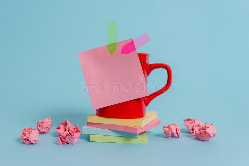 Το φλυτζάνι καφέ μπροστινής άποψης χρωμάτισε την κολλώδη να βρεθεί μαξιλαριών εγγράφου βελών σημειώσεων συντριμμένη εμβλήματα συσ στοκ φωτογραφίες