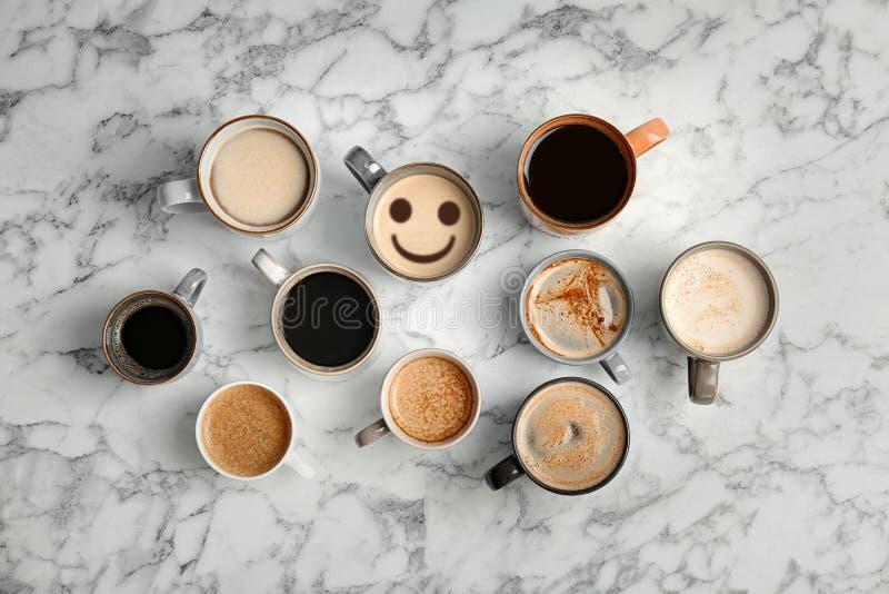 Το φλυτζάνι του εύγευστου καυτού καφέ με τον αφρό και του χαμόγελου μεταξύ άλλων στο μαρμάρινο υπόβαθρο, επίπεδο βάζει στοκ εικόνες