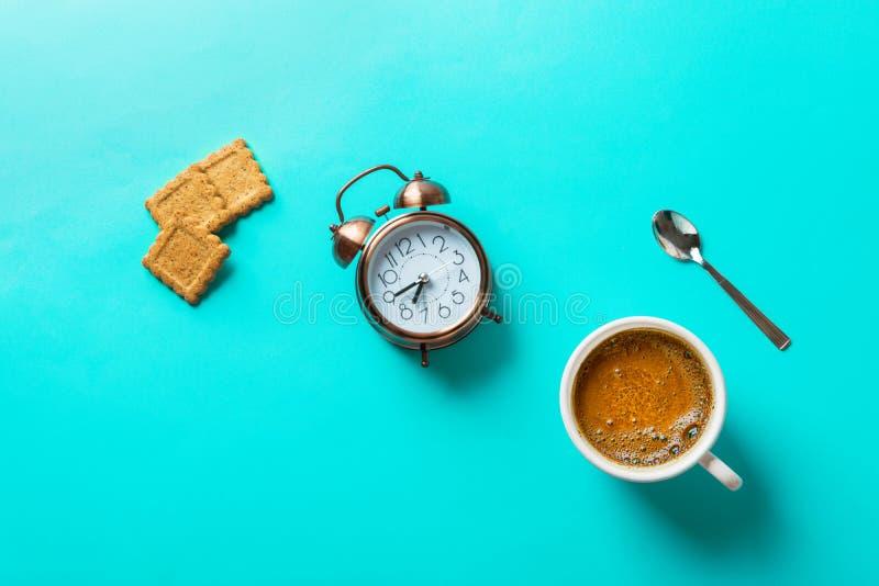 Το φλυτζάνι του πρόσφατα παρασκευασμένου καφέ με το σπίτι crema έψησε το κουτάλι ξυπνητηριών μπισκότων πίτουρου στο τυρκουάζ υπόβ στοκ φωτογραφία