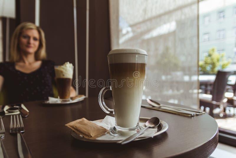 Το φλυτζάνι του caffe latte με τη νέα γυναίκα ομορφιάς κάθεται στο καφέ στοκ φωτογραφία με δικαίωμα ελεύθερης χρήσης