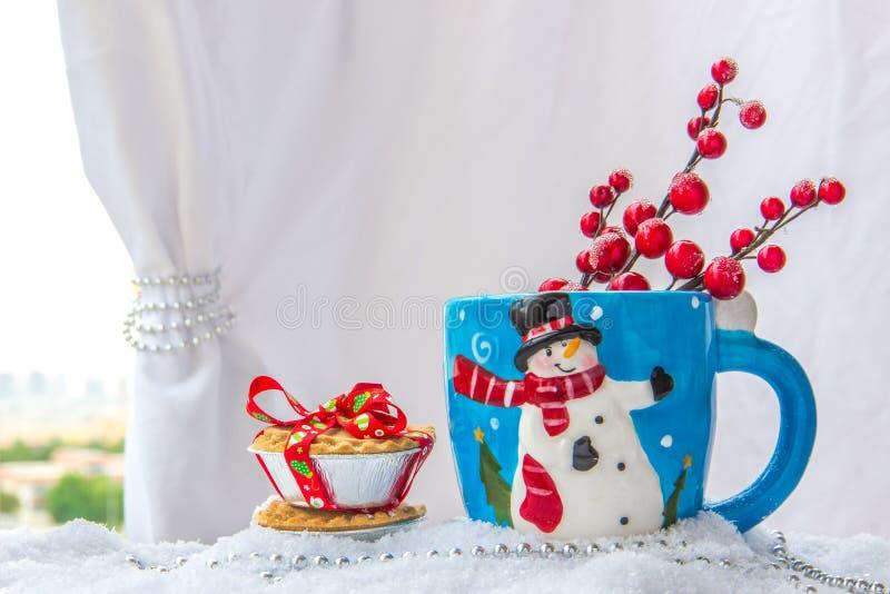 Το φλυτζάνι υποβάθρου Χριστουγέννων με έναν χιονάνθρωπο και τα φρούτα κομματιάζουν τις πίτες στοκ εικόνα