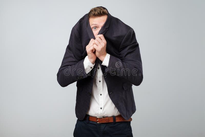 Το φοβισμένο νέο επιχειρησιακό άτομο κρύβει το πρόσωπό του από την επικίνδυνη επιχείρηση στο κοστούμι στοκ φωτογραφία