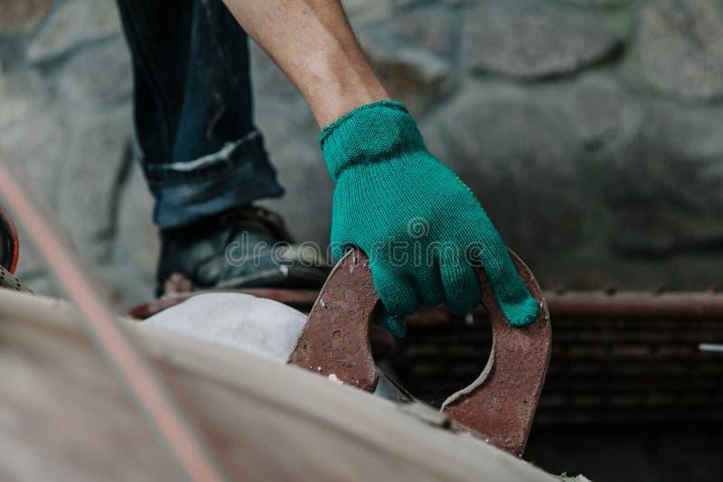 Το φορημένο γάντια χέρι κρατά επάνω στο μεγάλο μάτι της δομής μετάλλων στοκ φωτογραφία με δικαίωμα ελεύθερης χρήσης