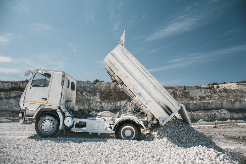 Το φορτηγό ξεφορτώνει το άσπρο αμμοχάλικο ασβεστόλιθων στο συντριμμένο λατομείο πετρών στοκ εικόνες