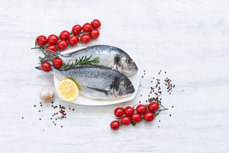 Το φρέσκια άψητη dorado ή η τσιπούρα αλιεύει με το λεμόνι, τα λαχανικά και τα καρυκεύματα πέρα από το άσπρο υπόβαθρο E στοκ φωτογραφίες με δικαίωμα ελεύθερης χρήσης