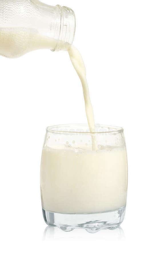 Το φρέσκο γάλα χύνεται από ένα μπουκάλι σε ένα γυαλί που απομονώνεται στοκ φωτογραφία με δικαίωμα ελεύθερης χρήσης