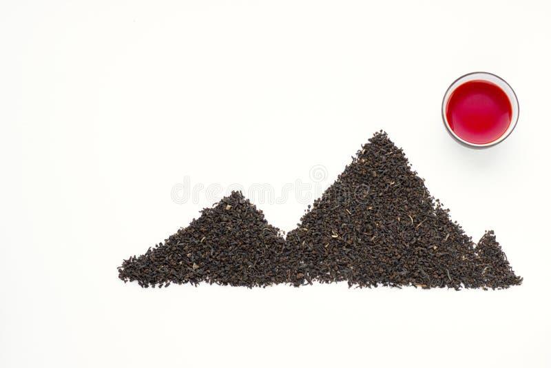Το φρέσκο κόκκινο τσάι τσαγιού Oolong σε ένα φλυτζάνι και το μαύρο τσάι διασκόρπισαν με μορφή των βουνών στοκ εικόνα με δικαίωμα ελεύθερης χρήσης