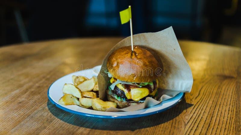 Το φρέσκο, νόστιμο, juicy χάμπουργκερ με το τυρί, ντομάτες, καρύκεψε το βόειο κρέας, το φρέσκες μαρούλι και τις πατάτες σε έναν ξ στοκ εικόνα με δικαίωμα ελεύθερης χρήσης